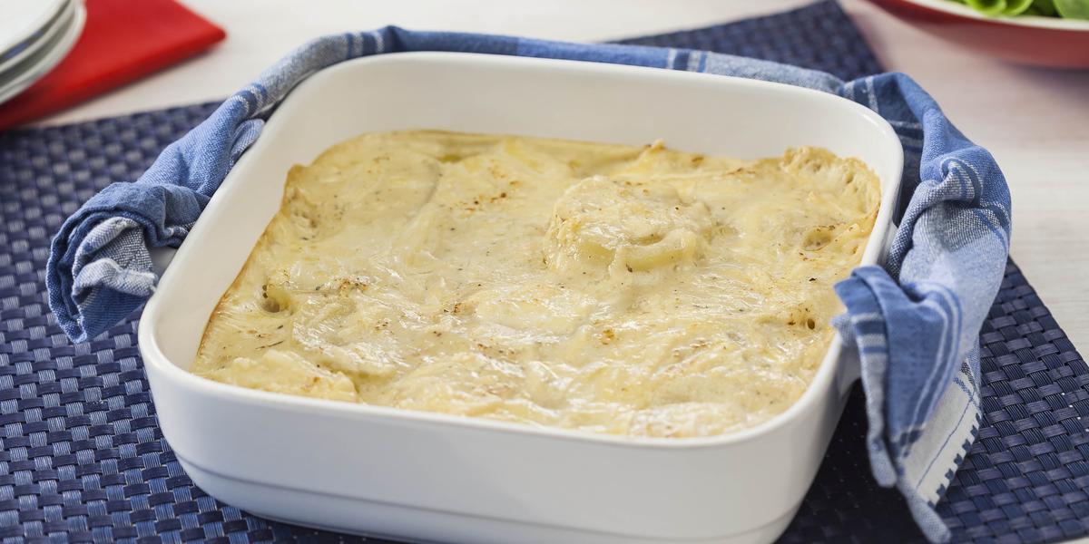 Fotografia em tons de azul e branco de uma bancada vista de cima. Contém um pano azul com um recipiente quadrado branco com alças e dentro as batatas gratinadas. Ao lado um pano azul.