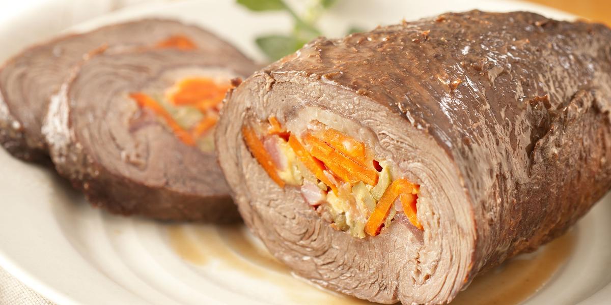 fotografia em tons de branco e laranja de uma bancada vista de frente. Contém um pano branco, um prato redondo com uma picanha recheada com cenoura, azeitona e bacon. Ao fundo um pote com um molho.