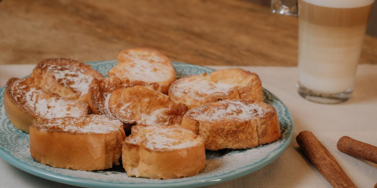 Fotografia em tons de marrom de uma bancada de madeira com um paninho branco sobre ele um prato azul claro e rabanas com açúcar e canela. Ao fundo paus de canela com um copo de leite.