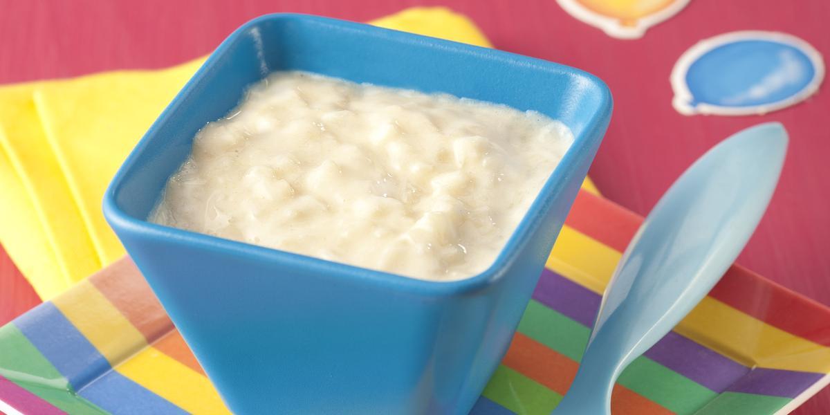 Fotografia em tons de rosa e amarelo em uma mesa de madeira rosa com um paninho amarelo, um prato listrado colorido com um potinho azul em cima dele com o creminho de frutas dentro. Ao lado, uma colher infantil azul.