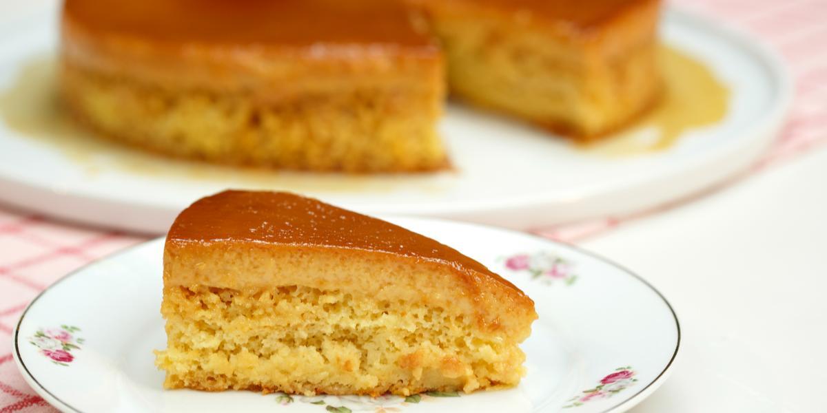 Fotografia em tons de branco e caramelo, com prato contendo fatia de bolo pudim sobre prato branco com borda decorada, ao fundo recipiente com bolo pudim fatiado, ambos sobre guardanapo branco e vermelho e bancada branca.