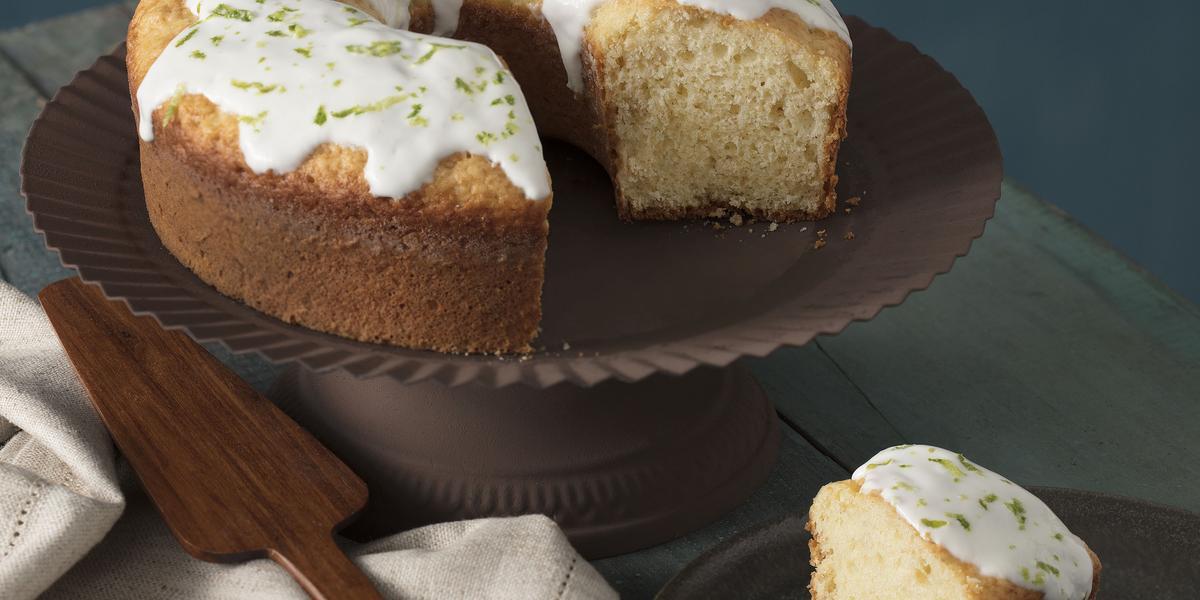 foto em tons de cinza, em uma mesa de madeira contém o bolo de iogurte ao lado um prato marrom com um pedaço de bolo um pano branco e por cima do pano uma espátula.