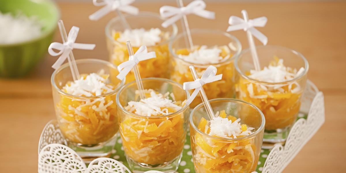 Fotografia em tons de laranja em uma mesa de madeira com um suporte de doces branco ao centro com os doces de abóbora em copinhos transparentes com palitinhos e um lacinho branco.