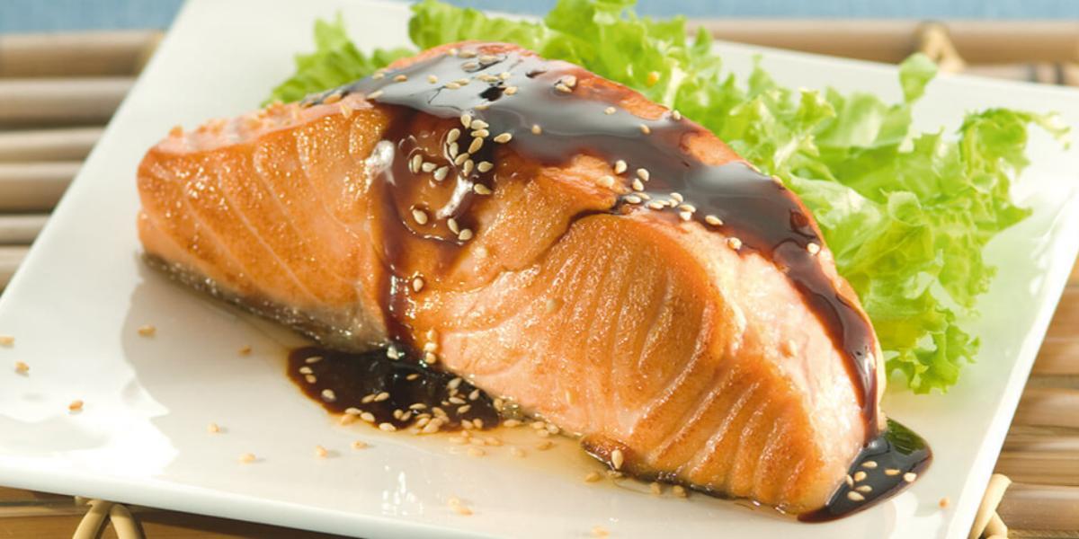 Fotografia em tons de azul e laranja de uma bancada azul vista de cima, um prato branco quadrado contém um pedaço de salmão com molho de soja shoyu e gergelim por cima e ao lado folhas de alface
