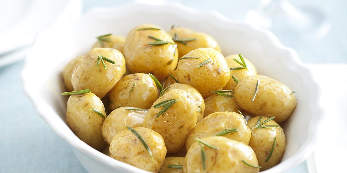 fotografia em tons de branca e azul de uma bancada vista de cima, contém um recipiente redondo e branco com bolinhas de batatas e alecrim por cima