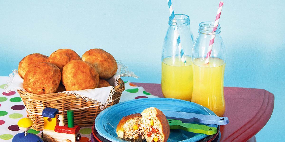 Fotografia em tons de azul e vermelho em uma mesa antiga vermelha com pratos coloridos, cesta de vime com os lanchinhos de frango sem leite e sem ovo e garrafas de vidro sobre a mesa.