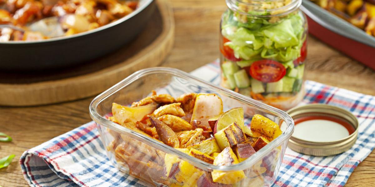 Fotografia em tons de madeira com um pano xadrez azul e vermelho, com um potinho de marmita com a batata-doce, mandioquinha e tiras de frango dentro dele.