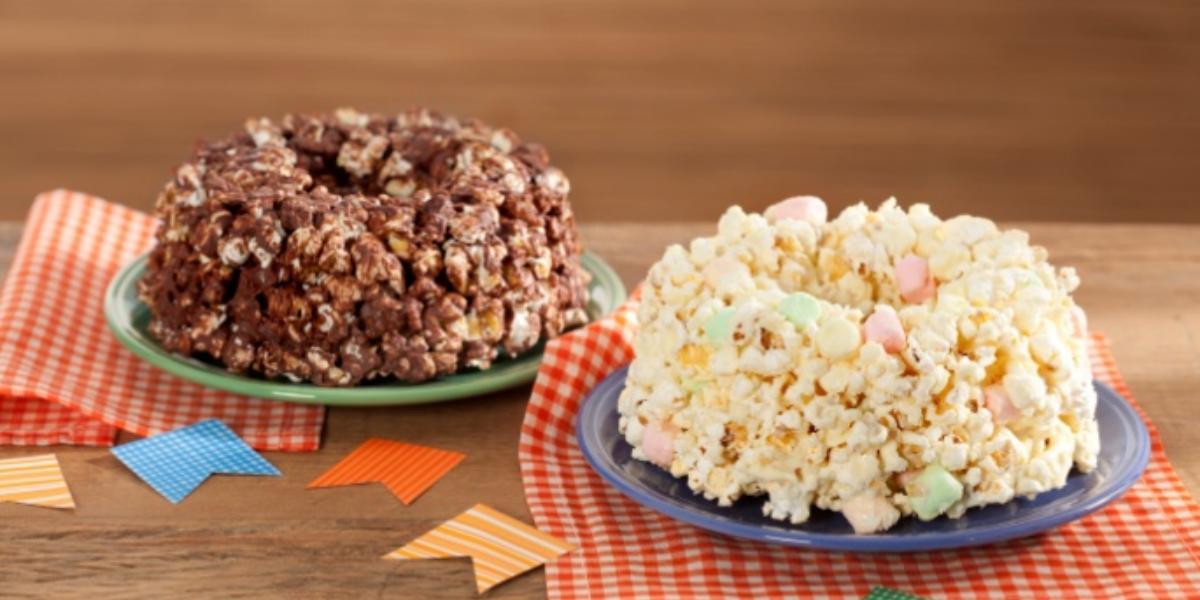 Fotografia em tons de vermelho em uma mesa de madeira com pano xadrez vermelho, um prato verde com o bolo de pipoca de chocolate e outro prato com o bolo de pipoca de chocolate branco.