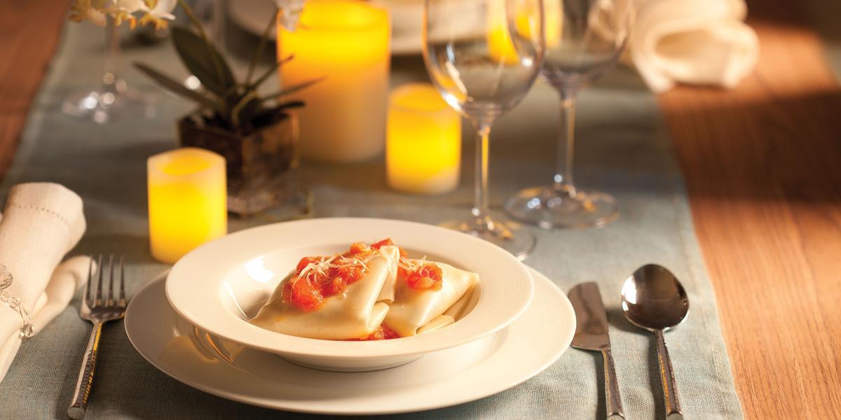 Fotografia em tons de amarelo em uma mesa de madeira e uma toalha de mesa cinza. Um sousplat branco e um prato fundo branco com a sofioli de shimeji ao molho de tomates. Velas amarelas, taças de vidro, arranjo pequeno de flor e talheres compondo a mesa.