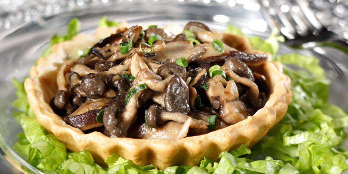 Fotografia em tons de verde e marrom, com torta de cogumelos sobre folhas verdes picadas em prato de vidro decorado, com garfo de inox ao lado.