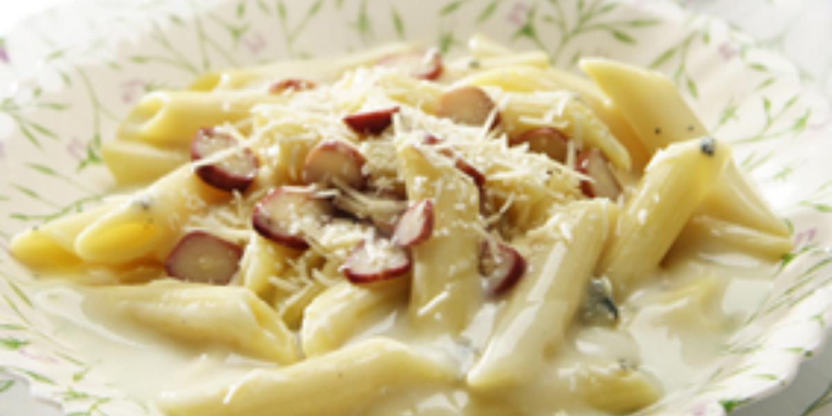 Fotografia tirada de uma prato redondo branco com macarrão e creme branco e pedaços de pinhões