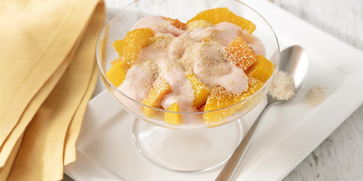 Fotografia em tons de branco e amarelo de uma bancada branca com um prato retangular branco, sobre ele uma taça com a salada de frutas e uma colher. Ao lado um paninho amarelo.