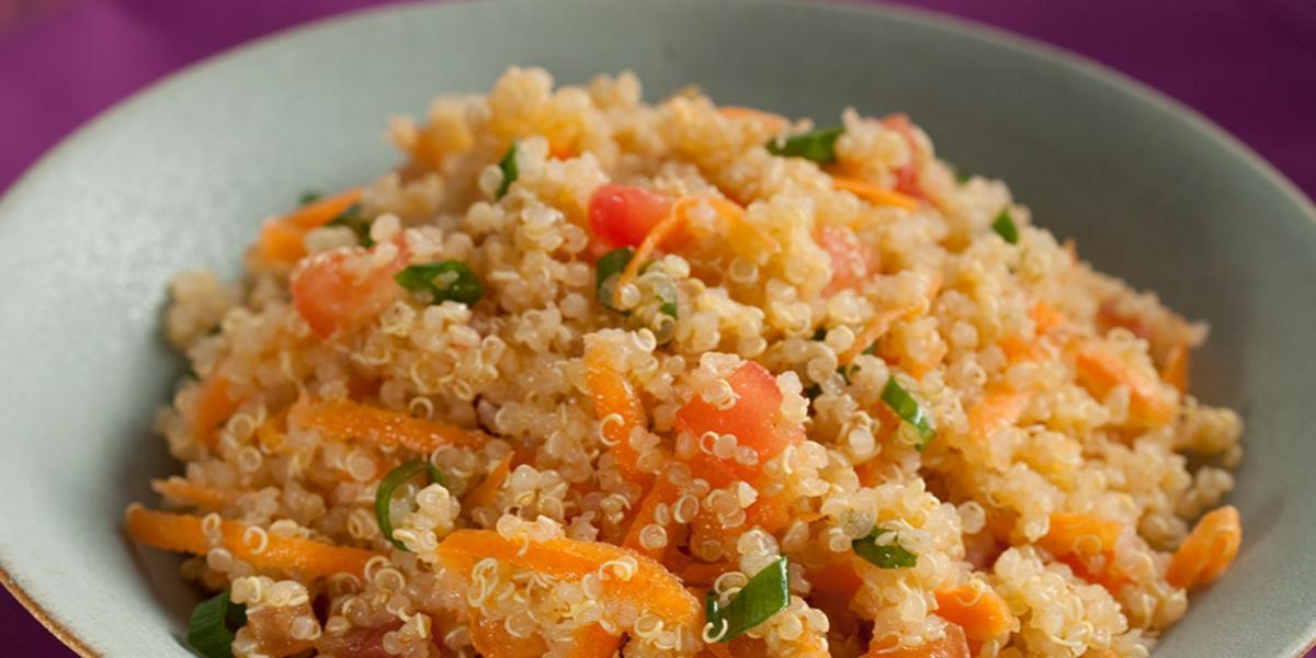 Fotografia em tons de laranja de uma bancada roxa com um prato fundo cinza com a salada de quinoa, tomate, cenoura ralada e cebolinha.