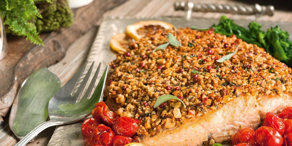 Fotografia de uma mesa posta onde o salmão está servido em uma bandeja de alumínio decorado com tomate cereja, limão siciliano e folhas a volta. Ao fundo a mesa de madeira está decorado com velas brancas acesas.