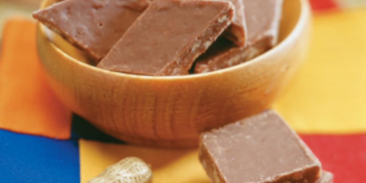 fotografia em tons de marrom, azul e amarelo. Contém um pote redondo marrom com pedaços quadrados de amendoim com chocolate.
