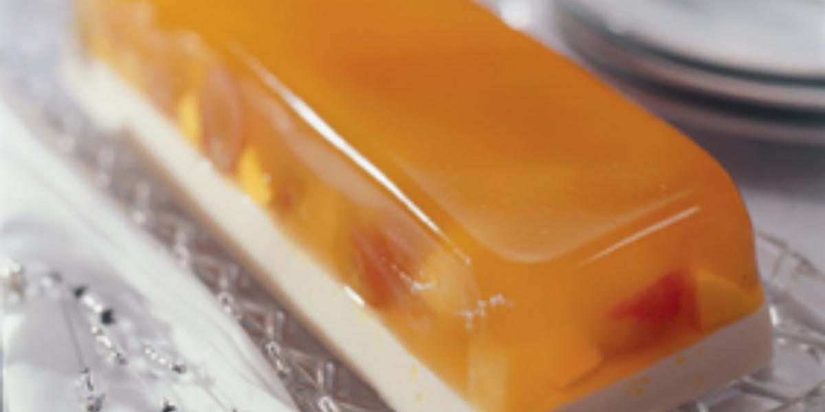 fotografia em tons de branco e laranja contém uma sobremesa gelada com camada de gelatina de frutas e pedaços de frutas.