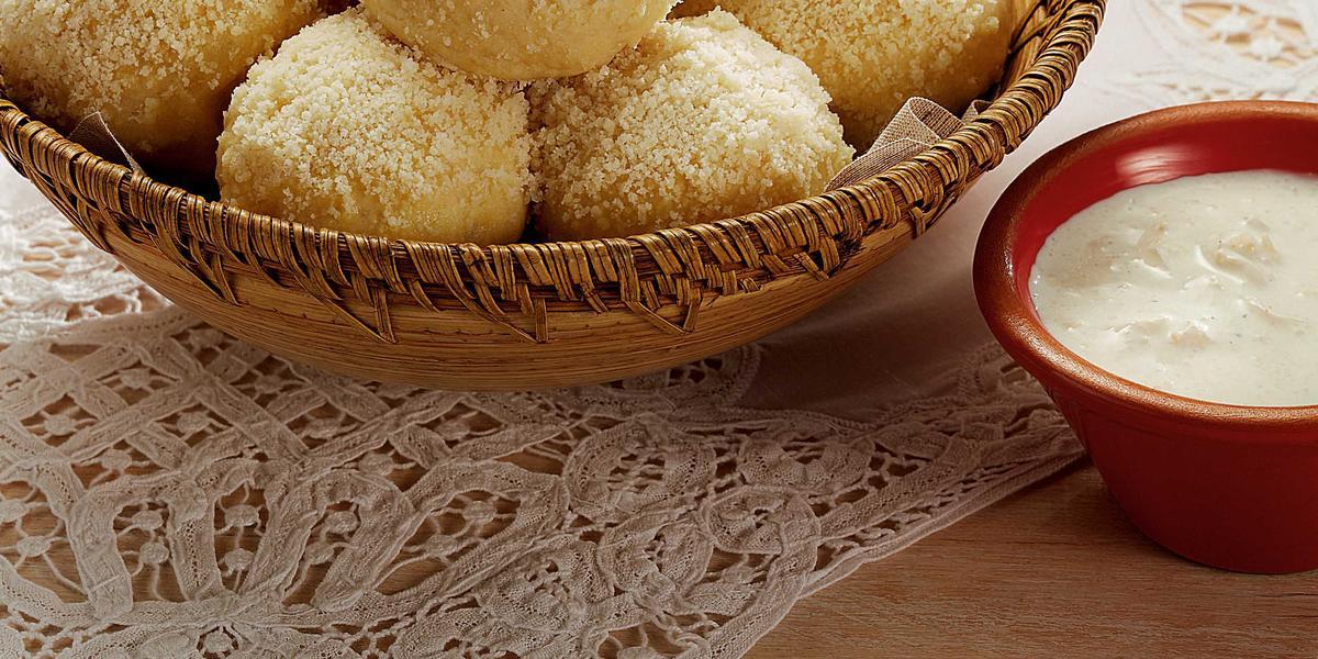 Fotografia em tons de branco, marrom, pardo e vermelho de uma bancada vista de cima. Um pano de renda branco e por cima um recipiente cor pardo e redondo com pães bolinha, ao lado um potinho vermelho redondo com creme branco.