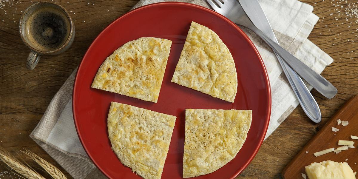 Fotografia em tons de vermelho em uma mesa de madeira com um prato vermelho ao centro com o pão de queijo de frigideira com aveia. Ao lado, talheres, trigo, centeio e uma xícara de café.