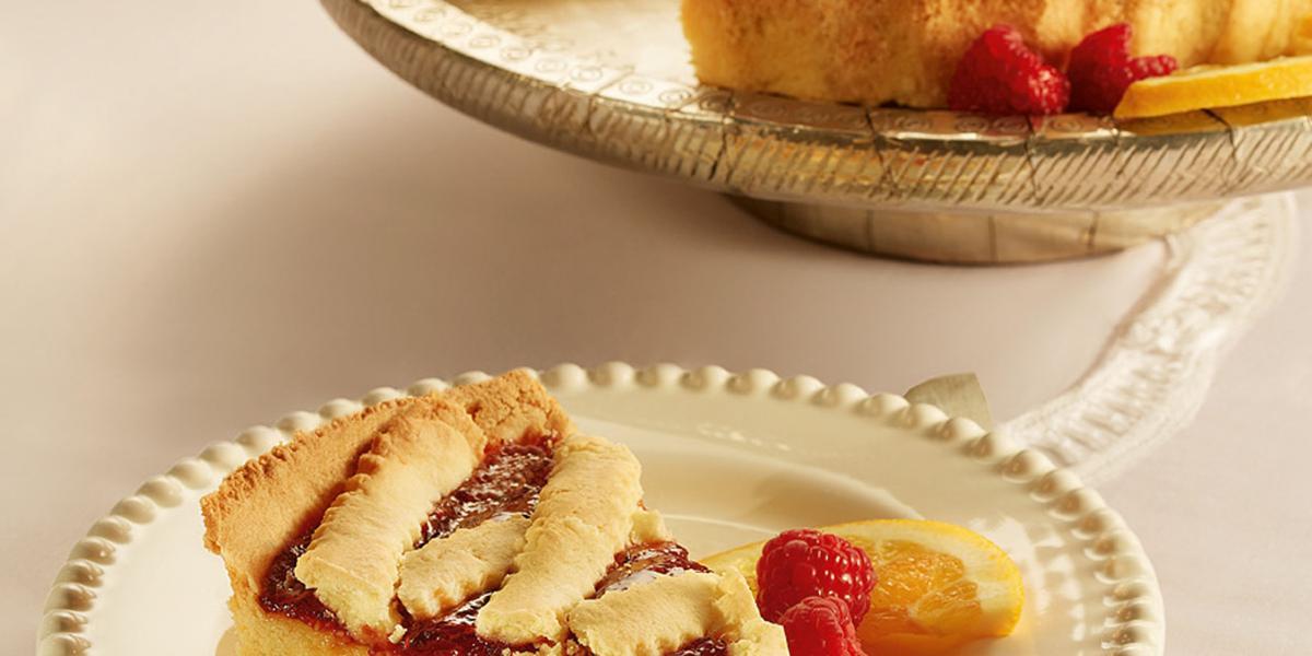 Fotografia em tons de bege em uma mesa de madeira, um guardanapo de pano bege e branco, um prato redondo branco com detalhes bege e uma fatia da crostata com recheio de laranja. Ao fundo, um prato redondo maior com a crostata inteira.