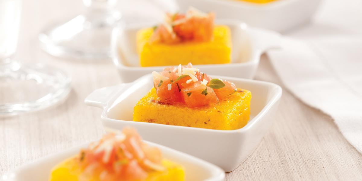 Fotografia em tons de laranja em uma bancada de madeira clara, um pano bege, quatro potinhos brancos pequenos com a polenta com tomate dentro de cada um.