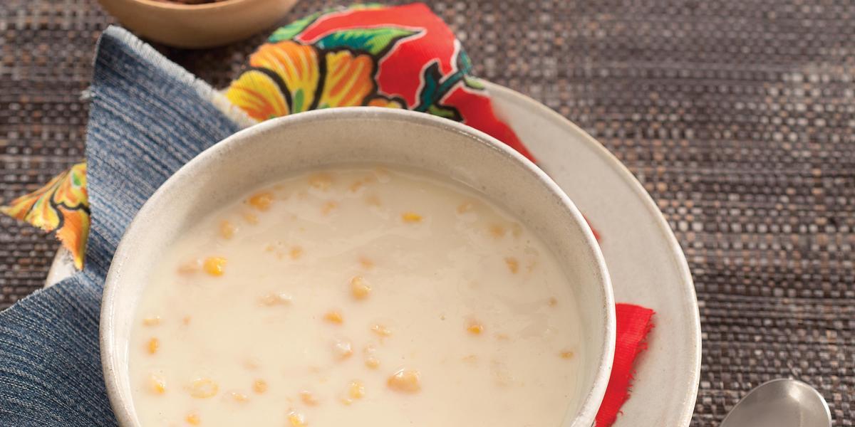 Fotografia em tons de cinza e  branco de um paninho cinza, sobre ele um prato redondo branco raso  com um paninho estampado, sobre ele um prato redondo fundo branco com a canjica. Ao lado uma faca com cabo de madeira. Ao fundo dois potinhos com