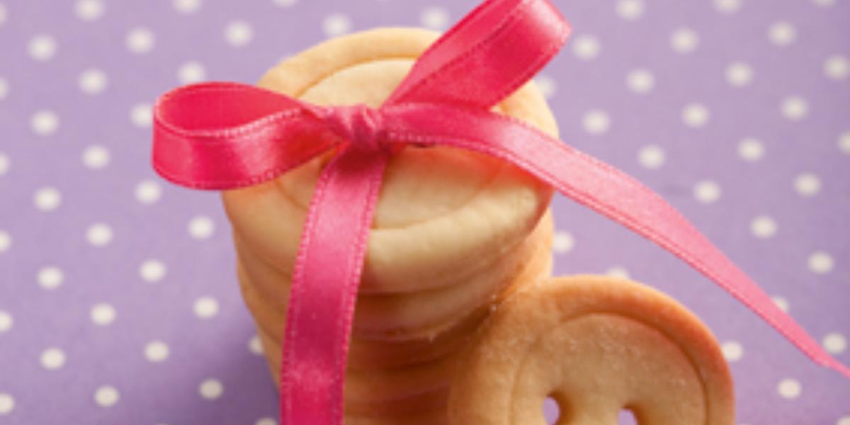 fotografia em tons de roxo, bege e rosa de uma bancada roxa com bolinhas brancas, contém biscoitinhos em formatos de botão com um laço rosa por cima.
