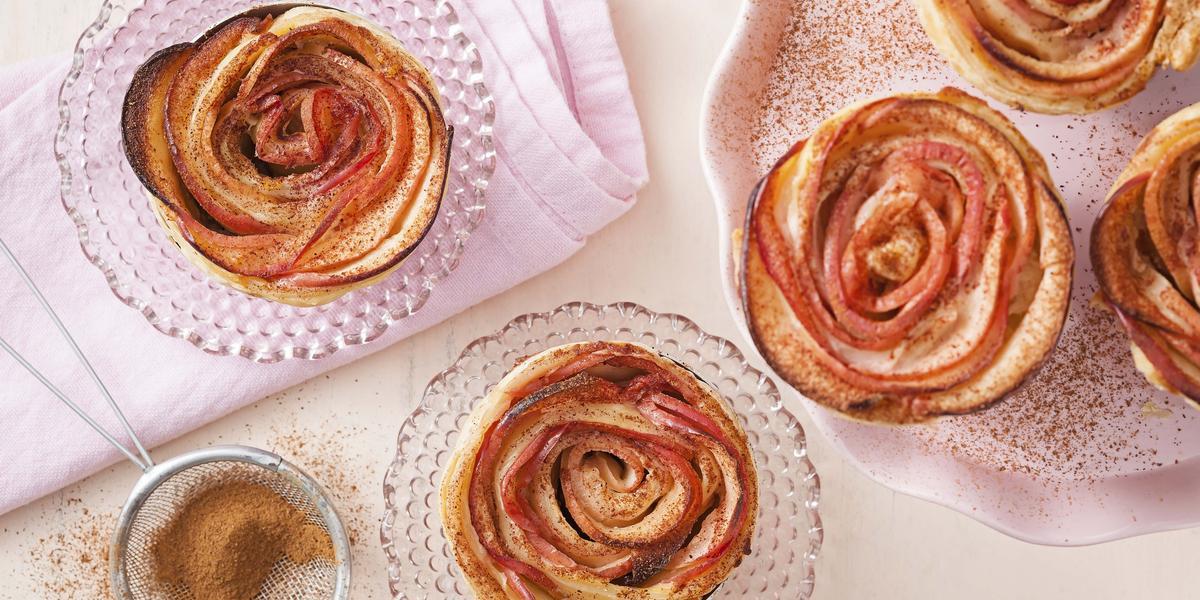 Fotografia em tons de rosa, vermelho e dourado com tortinhas de maçã sobre pratinhos de cristal sobre guardanapo rosa, prato branco com três tortinhas, peneirinha com canela em pó, tudo sobre bancada em tom de rosa.