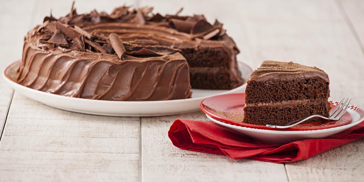 Fotografia em tons chocolate e branco, ao centro prato com bolo de chocolate fatiado, fatia ao lado sobre pratos vermelho e branco com um garfo e sobre guardanapo vermelho, tudo sobre bancada de madeira em pátina.