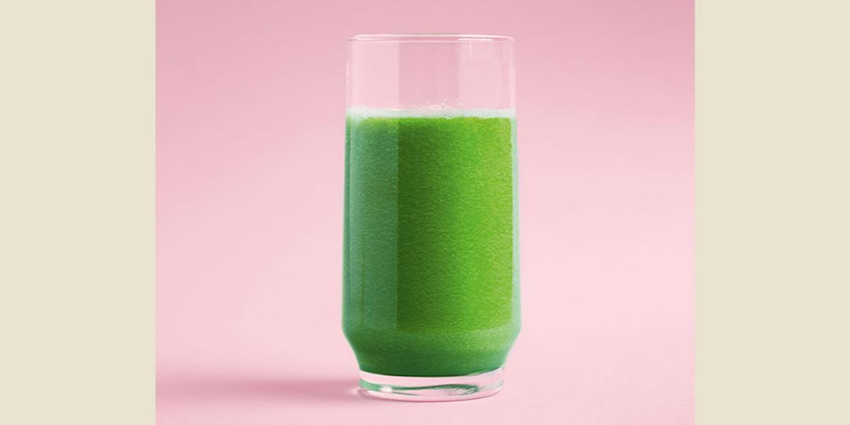 Fotografia em tons de verde e rosa, com copo de suco verde ao centro, em plano rosa.