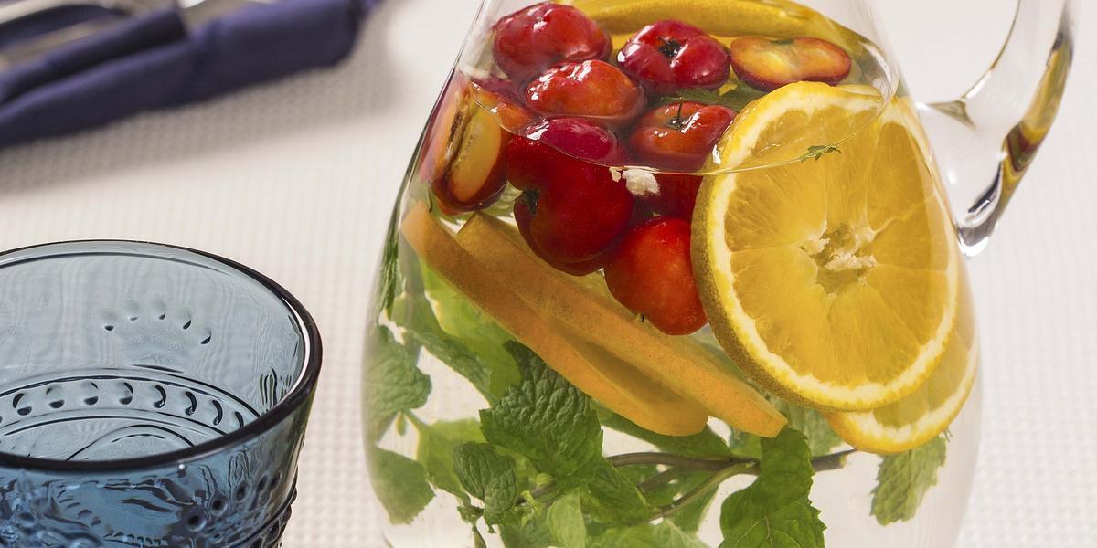fotografia em tons de branco e azul de uma bancada vista de cima, uma jarra transparente com agua, pedaços de laranja, acerola e hortelã e ao lado um copo cor azul para servir