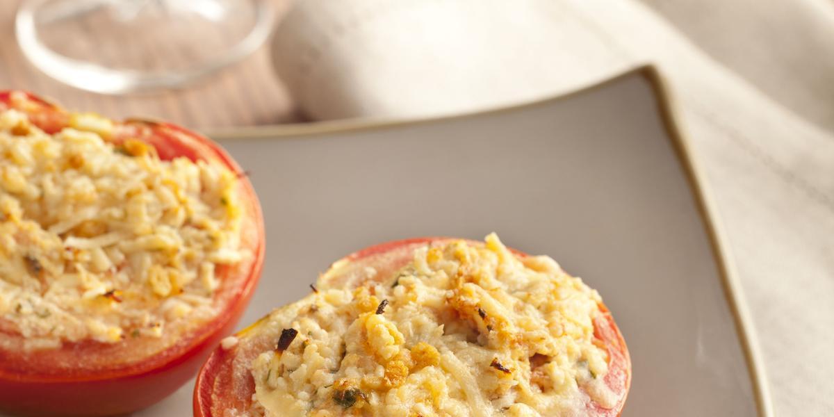 Fotografia em tons de vermelho e bege, em uma mesa de madeira a receita de tomate recheado é servida em um prato branco, e para decorar  um guardanapo branco com taças ao fundo
