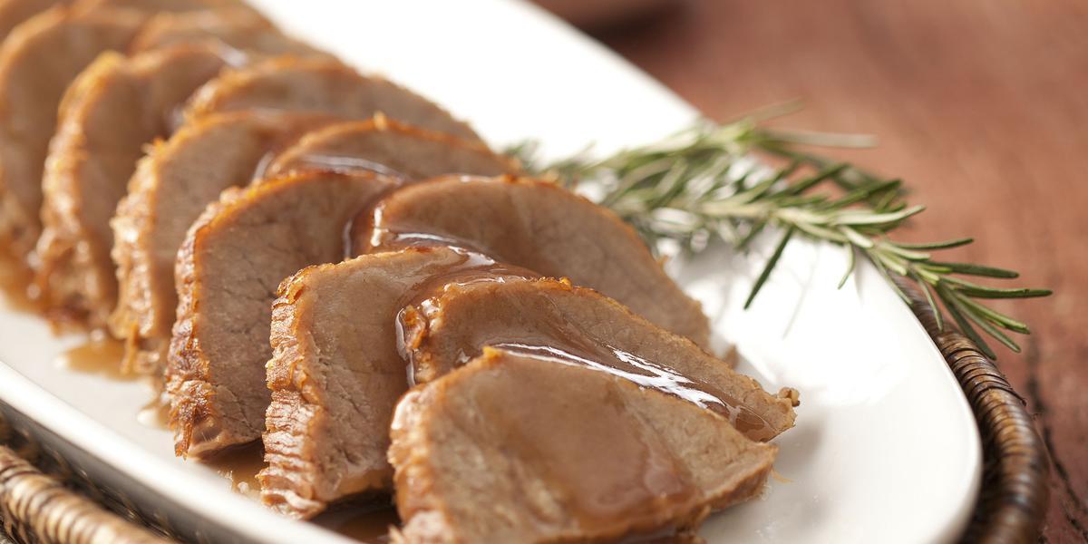 foto em tons marrom e branco. Uma mesa de madeira contém um cesto com um prato que comporta pedaços de carne fatiados.