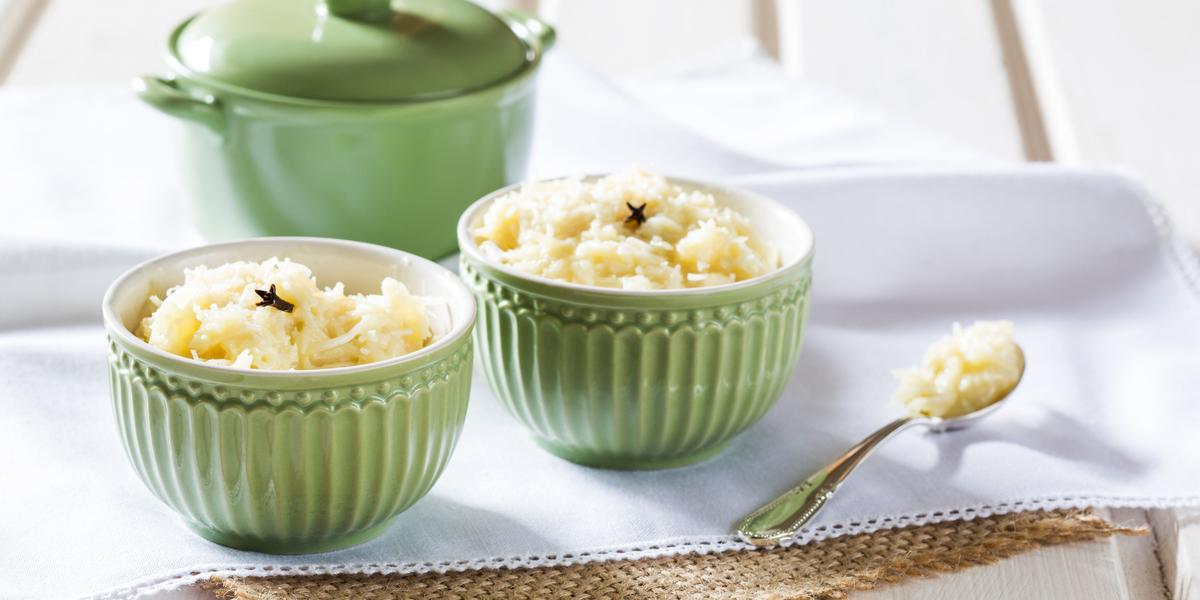 Fotografia de dois potinhos verdes com cocada dentro e uma colher de chá com cocada sobre guardanapos branco e bege, ao lado potinho verde com tampa, tudo sobre uma bancada branca.