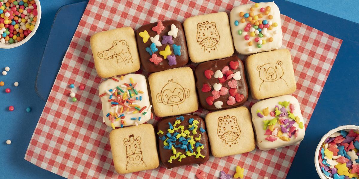 Fotografia em tons de azul e vermelho de uma bancada azul com paninho xadrez vermelho e branco sobre ele biscoitos Passatempo cobertos com chocolate e confeitos coloridos. Ao lado três recipientes brancos redondos com confeitos coloridos.
