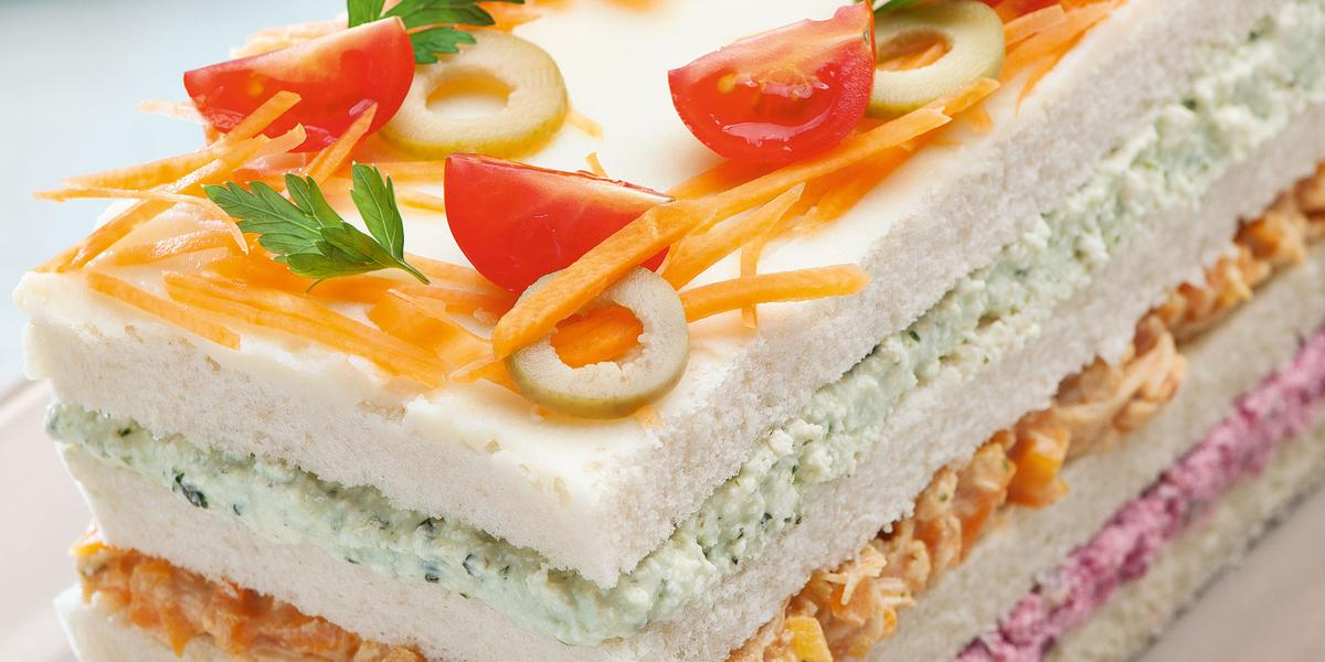 Fotografia do torta fria retangular, feita com pão de forma, e cores rosa, laranja e verdes no recheio, para decoração tomate cereja, cenoura e azeitona. A torta está sendo servida em um parto retangular rosa claro.