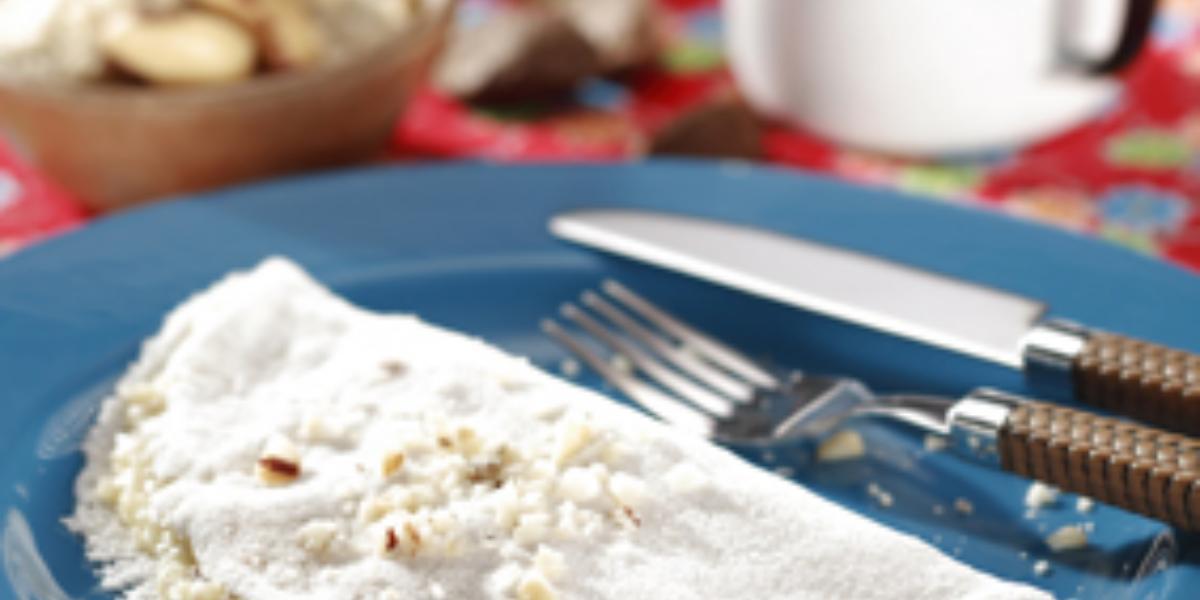 fotografia em tons de azul, branco e vermelho de uma bancada forrada com um pano vermelho e por cima um prato redondo azul com a tapioca e garfo e faca ao lado para servir.