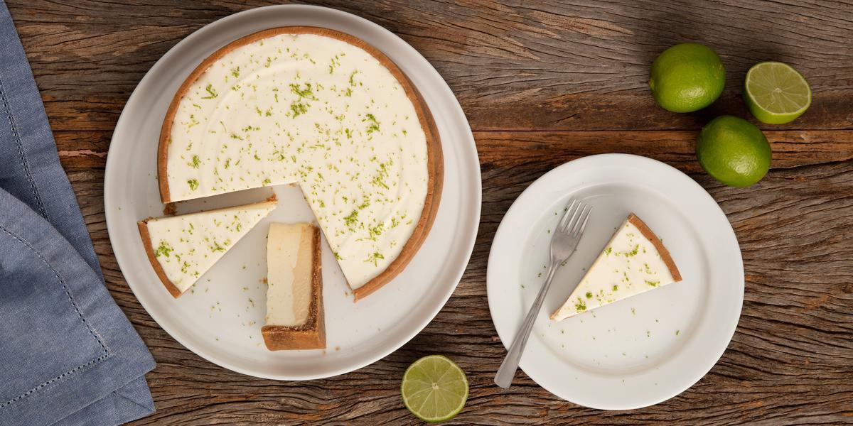 Fotografia em tons de branco e marrom de uma bancada de madeira vista de cima, com um prato branco com uma torta de limão fatiada, ao lado direito prato com uma porção de torta com um garfo e limões, e no esquerdo um guardanapo azul.