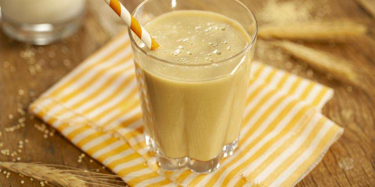Fotografia em tons de marrom e amarelo de uma bancada de madeira com paninho listrado amarelo e branco, sobre ele um copo de vidro com a vitamina deliciosa e um canudo listrado amarelo e branco. Ao fundo ramos de trigo.