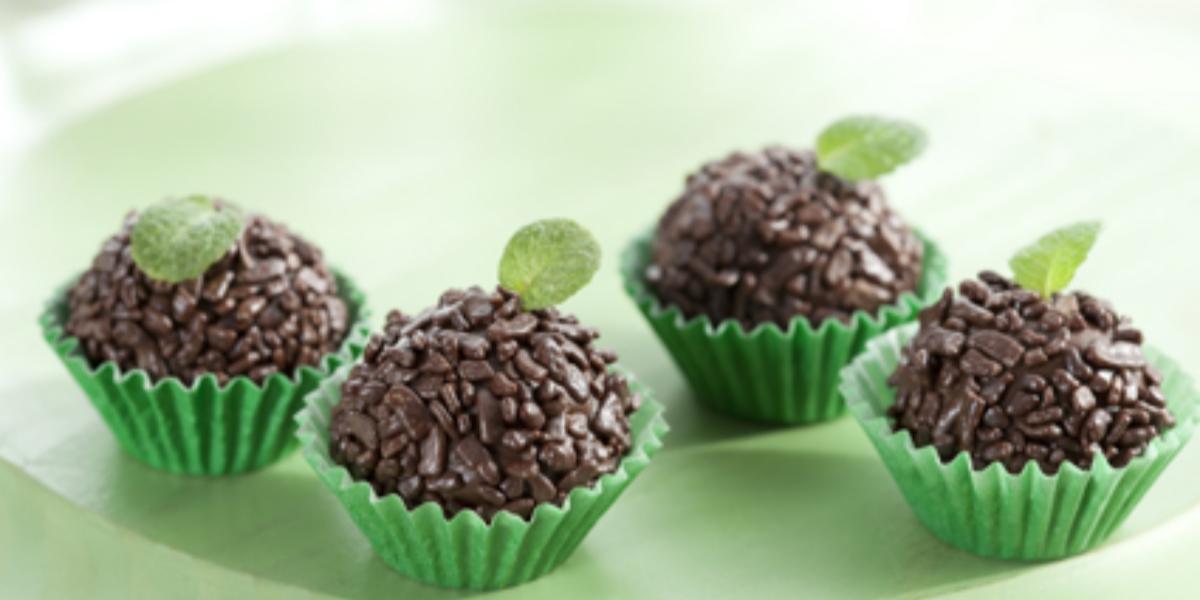 fotografia em tons de verde e marrom, contém 4 brigadeiros com granulados por cima dentro de forminhas verdes e todos tem uma folha de hortelã por cima para decorar