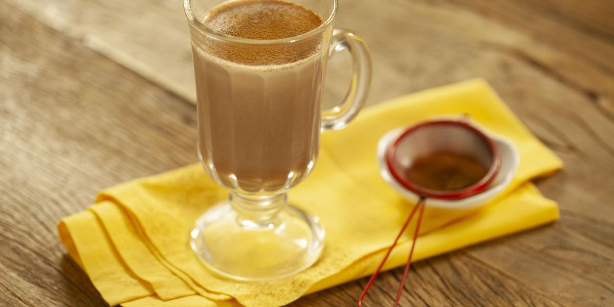 Fotografia em tons de marrom e amarelo de uma bancada de madeira com um paninho amarelo, sobre ele uma xícara transparente com leite, chocolate baton derretido e canela em pó. Ao lado uma peneira vermelha com canela.