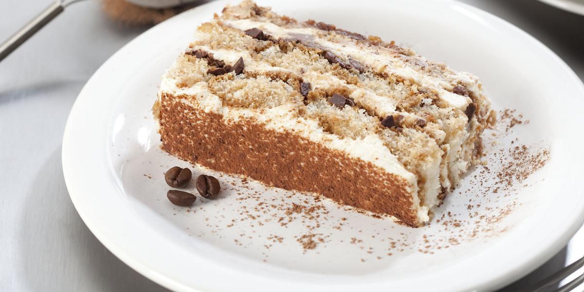 Fotografia em tons de branco, marrom e cinza, com prato branco ao centro com porção de bolo fatiado, no entorno garfo, peneirinha com chocolate em pó e pratos brancos empilhados, tudo sobre bancada em tons de cinza.