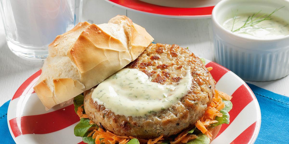 foto em tons de branco, azul e vermelho de uma bancada branca vista de cima, contém um pano azul com dois pratos em tons de branco e vermelho e ambos contém um pão com Hambúrguer