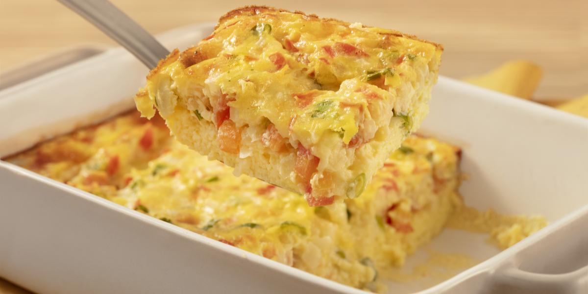 Fotografia em tons de branco e amarelo de uma bancada de madeira clara com um paninho amarelo sobre ele um recipiente quadrado branco com o omelete de forno e uma espátula retirando um pedaço de omelete.