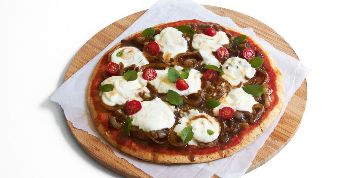 Ao centro, uma tábua de madeira marrom redonda com um pano branco e uma pizza com tomates, cebolas e iogurte por cima.
