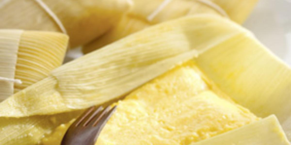 Fotografia em tons de amarelo em uma bancada de madeira, uma toalha colorida florida e algumas pamonhas de queijo coalho e alecrim em cima da bancada.
