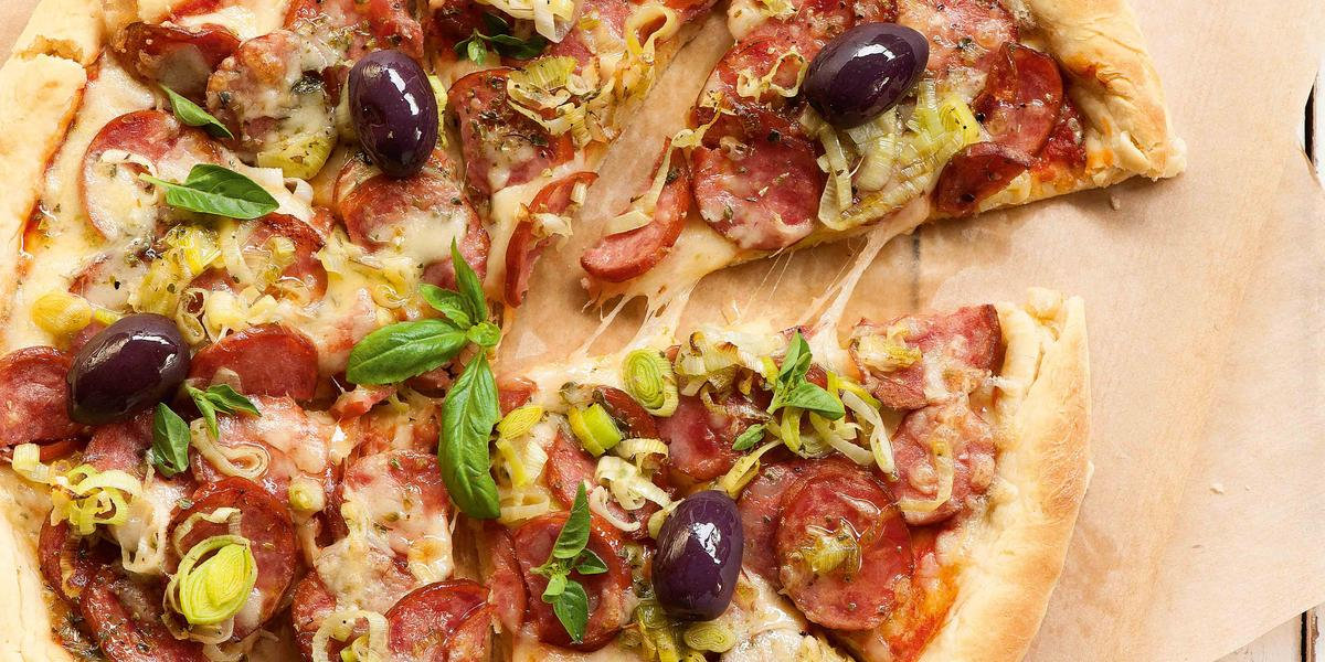Fotografia em tons de marrom e vermelho de uma bancada de madeira branco com um paninho marrom claro, sobre ele uma pizza de calabresa e uma espátula retirando uma fatia. Ao lado um recipiente redondo amarelo com manjericão.