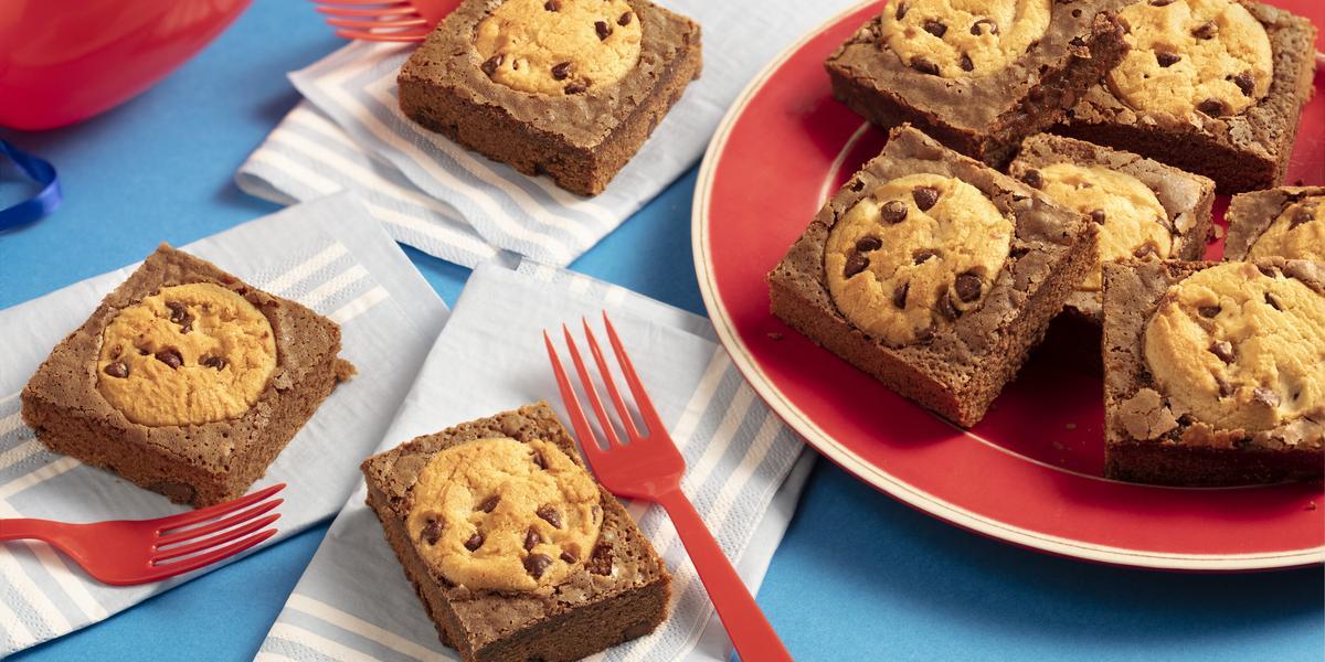 Fotografia em tons de azul e vermelho de uma bancada azul com paninhos azul claro com listras brancas e sobre eles pedaços de brownie com cookies e garfos vermelhos. Ao lado um prato vermelho e sobre eles pedaços de brownie com cookies.