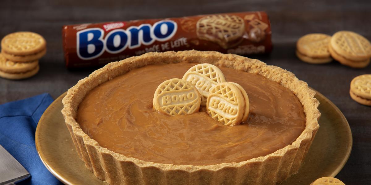 Foto de uma torta de doce de leite de cores marrom clara e escura. Ela está sobre um prato marrom, numa mesa com um tecido azul e uma espátula de bolo de aço inox. Há biscoitos Bono Doce de Leite espalhados e ao fundo um pacote de Biscoito Bono