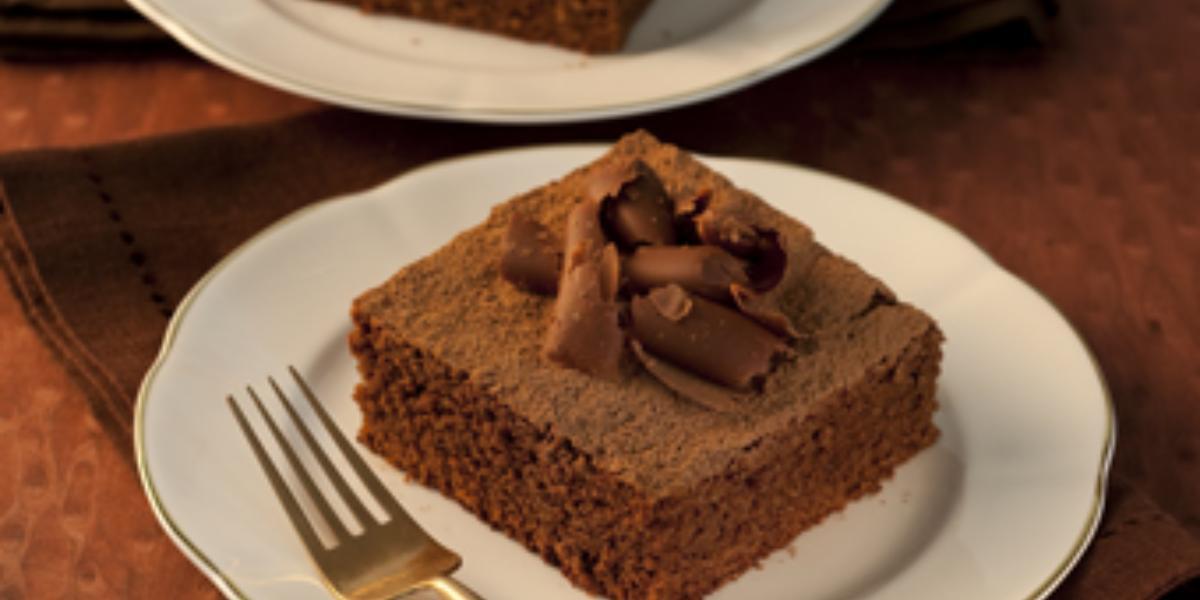 Fotografia em tons de marrom em uma mesa de madeira escura com dois pratos rasos brancos com dois pedaços do bolo de chocolate decorado com raspas de chocolate.