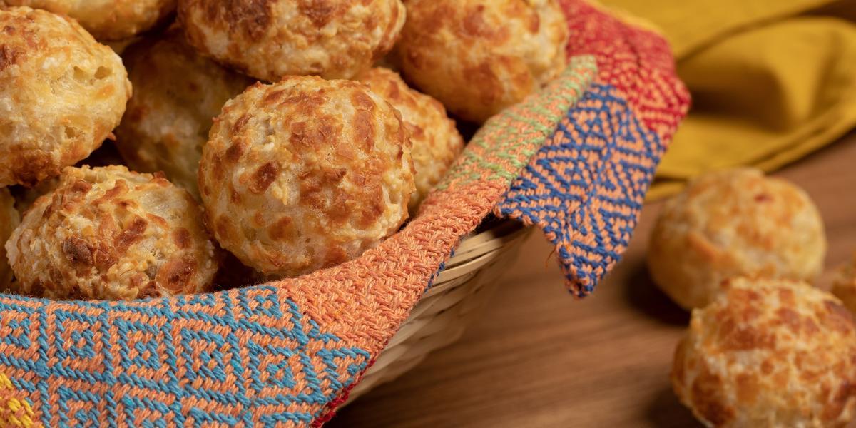 Foto de uma bancada de madeira. Sobre ela, bem próximo, está uma cesta com um tecido colorido e, dentro dela, diversos pães de queijo dourados. Na bancada ainda há dois pães de queijo solto e um tecido amarelo ao fundo